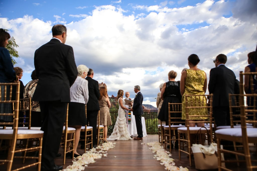 sedona destination wedding bride and groom take their vows outdoors under blue sky mountain backdrop